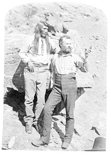 John Wesley Powell hiding his amputated right arm behind his Paiute messenger Tau-gu